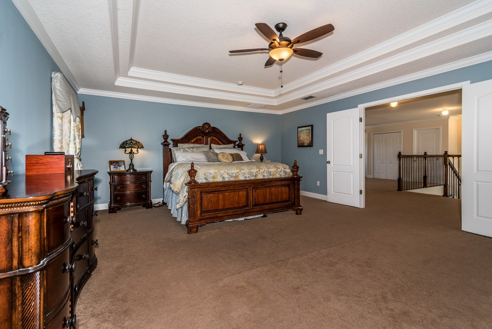 master bedroom with double tray ceilings and views of the lake